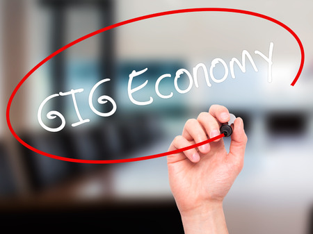 independent contractor: Man Hand writing GIG Economy with black marker on visual screen. Isolated on background. Business, technology, internet concept. Stock Photo