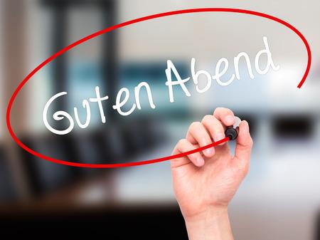 cansancio: Hombre de la mano escribiendo Guten Abend (buena tarde en alemán) con marcador negro en la pantalla visual. Aislado en el fondo. Negocios, la tecnología, el concepto de internet. Foto de stock