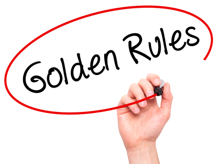 Man Hand writing Golden Rules with black marker on visual screen. Isolated on white. Business, technology, internet concept. Stock Photo Stock Photo