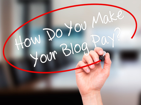 adwords: Man Hand writing How Do You Make Your Blog Pay? with black marker on visual screen. Isolated on office. Business, technology, internet concept. Stock Photo Stock Photo