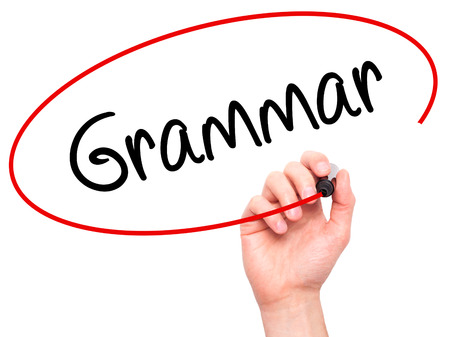 Man Hand writing Grammar with black marker on visual screen. Isolated on background. Business, technology, internet concept. Stock Photo Standard-Bild
