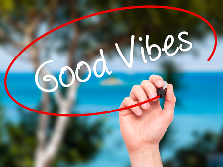 philosophy of music: Man Hand writing Good Vibes with black marker on visual screen. Isolated on nature. Business, technology, internet concept. Stock Photo