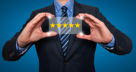 hotel reviews: Businessman holding five star rating. Blue - Stock Image
