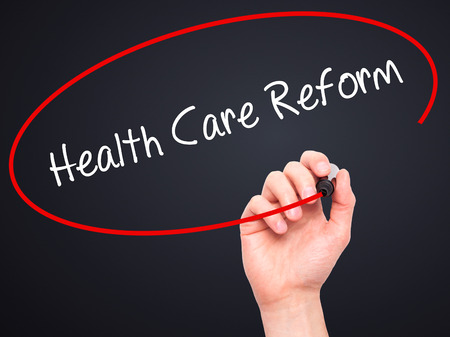 obama care: Man Hand writing Health Care Reform with black marker on visual screen. Isolated on black. Business, technology, internet concept. Stock Photo