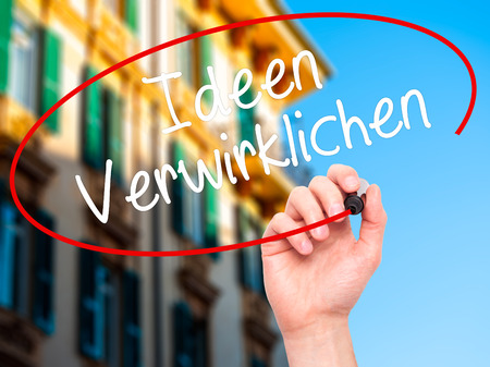seeking solution: Man Hand writing Ideen Verwirklichen ( Realize Ideas in German) with black marker on visual screen. Isolated on background. Business, technology, internet concept. Stock Photo