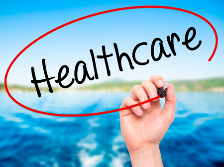 mandated: Man Hand writing Healthcare with black marker on visual screen. Isolated on nature. Business, technology, internet concept. Stock Photo Stock Photo