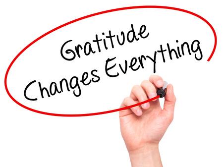 Man mano che scrive Gratitude cambia tutto con un pennarello nero sullo schermo visivo. Isolato su bianco Affari, tecnologia, concetto di internet. Foto d'archivio Archivio Fotografico