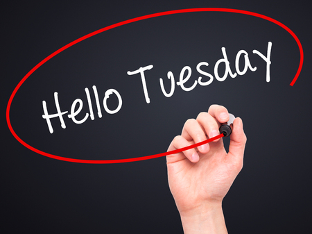 Man Hand writing Hello Tuesday with black marker on visual screen. Isolated on black. Business, technology, internet concept. Stock Photo
