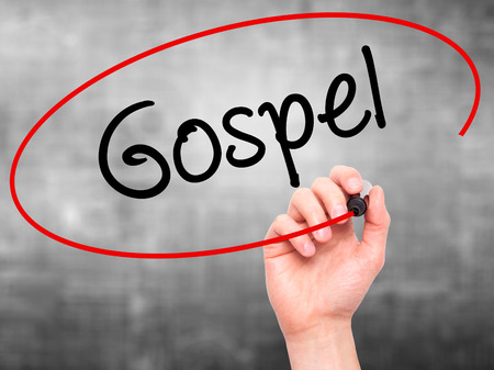 dogma: Man Hand writing Gospel  with black marker on visual screen. Isolated on background. Business, technology, internet concept. Stock Photo