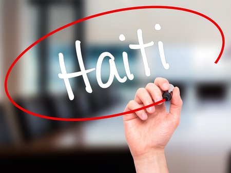 Man Hand writing Haiti with black marker on visual screen. Isolated on office. Business, technology, internet concept. Stock Photo Stock Photo