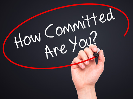 committed: Man Hand writing How Committed Are You? with black marker on visual screen. Isolated on black. Business, technology, internet concept. Stock Photo