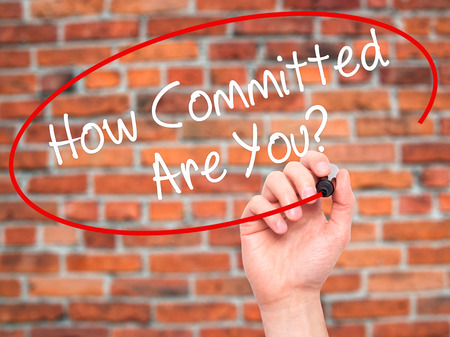 committed: Man Hand writing How Committed Are You? with black marker on visual screen. Isolated on bricks. Business, technology, internet concept. Stock Photo Stock Photo