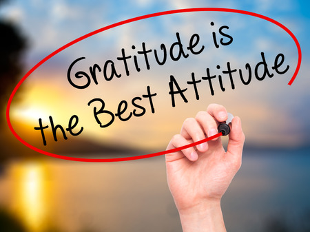 positiveness: Man Hand writing Gratitude is the Best Attitude with black marker on visual screen. Isolated on nature. Business, technology, internet concept. Stock Photo