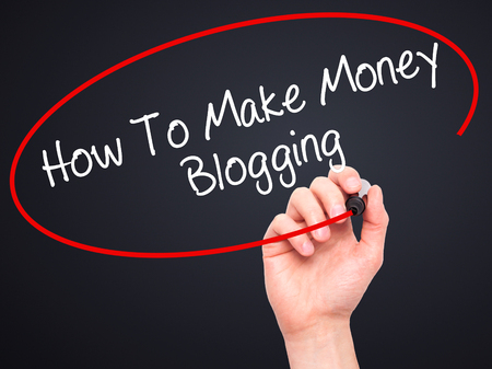 monetization: Man Hand writing How To Make Money Blogging with black marker on visual screen. Isolated on black. Business, technology, internet concept. Stock Photo
