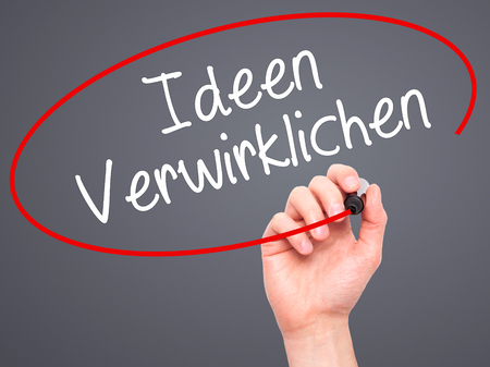 realize: Man Hand writing Ideen Verwirklichen ( Realize Ideas in German) with black marker on visual screen. Isolated on background. Business, technology, internet concept. Stock Photo