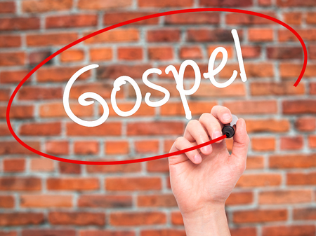credo: Man Hand writing Gospel  with black marker on visual screen. Isolated on background. Business, technology, internet concept. Stock Photo