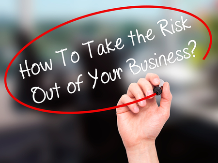 security safety: Man Hand writing How To Take the Risk Out of Your Business? with black marker on visual screen. Isolated on office. Business, technology, internet concept. Stock Photo Stock Photo