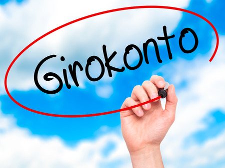 girokonto: Man Hand writing  Girokonto (Checking Account) with black marker on visual screen. Isolated on background. Business, technology, internet concept. Stock Photo Stock Photo