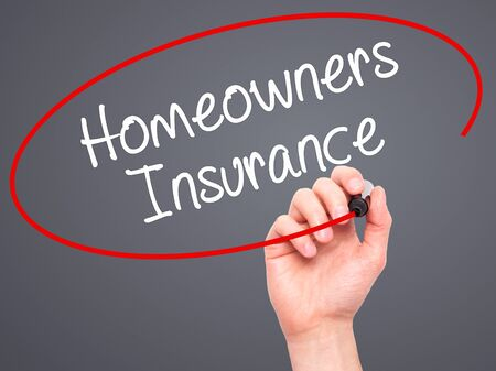 homeowners: Man Hand writing Homeowners Insurance with black marker on visual screen. Isolated on background. Business, technology, internet concept. Stock Photo
