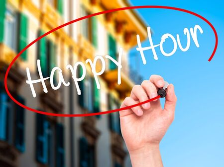 working hour: Man Hand writing Happy Hour with black marker on visual screen. Isolated on city. Business, technology, internet concept. Stock Image Stock Photo