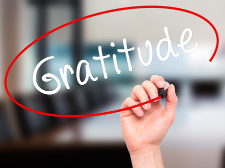 compassionate: Man Hand writing Gratitude with black marker on visual screen. Isolated on office. Business, technology, internet concept. Stock Photo