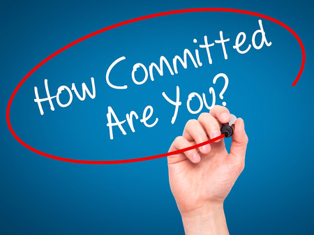 committed: Man Hand writing How Committed Are You? with black marker on visual screen. Isolated on blue. Business, technology, internet concept. Stock Photo