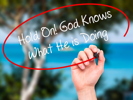 confessing: Man Hand writing Hold On! God Knows What He is Doing with black marker on visual screen. Isolated on nature. Business, technology, internet concept.