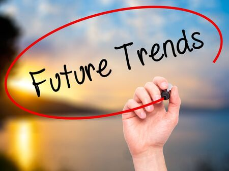 tendency: Man Hand writing Future Trends with black marker on visual screen. Isolated on nature. Business, technology, internet concept.