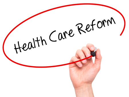 obama care: Man Hand writing Health Care Reform with black marker on visual screen. Isolated on white. Business, technology, internet concept. Stock Photo