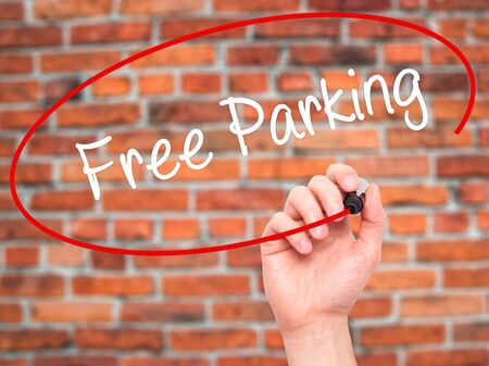 visual screen: Man Hand writing Free Parking with black marker on visual screen. Isolated on bricks. Business, technology, internet concept. Stock Photo Stock Photo