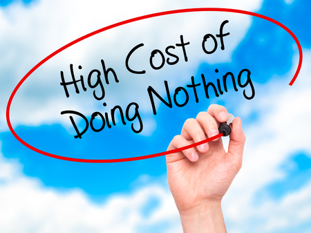 high cost: Man Hand writing High Cost of Doing Nothing with black marker on visual screen. Isolated on sky. Business, technology, internet concept. Stock Photo Stock Photo