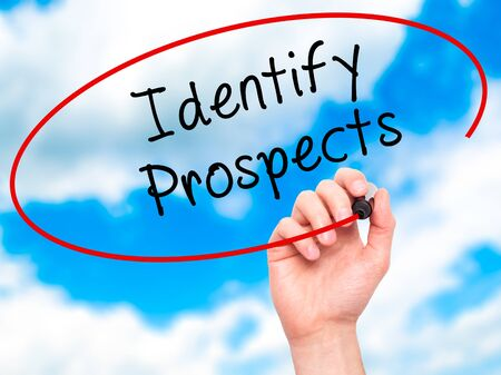prospecting: Man Hand writing Identify Prospects with black marker on visual screen. Isolated on sky. Business, technology, internet concept. Stock Photo