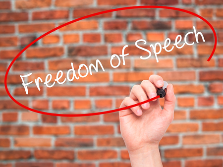 silenced: Man Hand writing Freedom of Speech with black marker on visual screen. Isolated on bricks. Business, technology, internet concept. Stock Photo