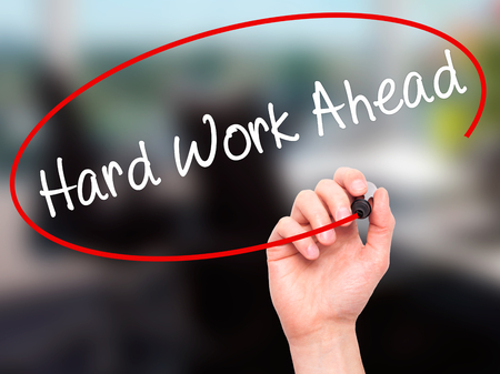 work ahead: Man Hand writing Hard Work Ahead with black marker on visual screen. Isolated on office. Business, technology, internet concept. Stock Photo