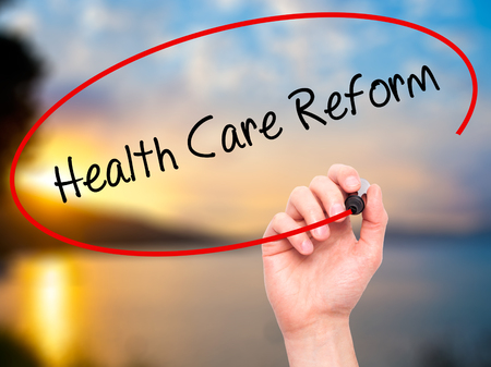 hmo: Man Hand writing Health Care Reform with black marker on visual screen. Isolated on nature. Business, technology, internet concept.