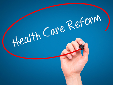 obama care: Man Hand writing Health Care Reform with black marker on visual screen. Isolated on blue. Business, technology, internet concept. Stock Photo