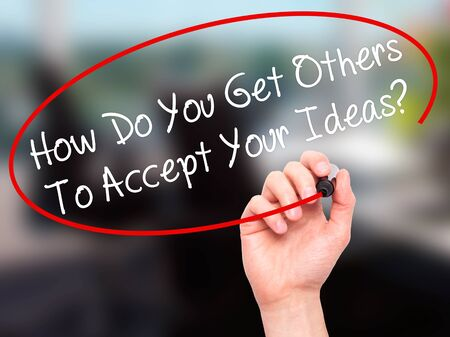 persuasiveness: Man Hand writing How Do You Get Others To Accept Your Ideas? with black marker on visual screen. Isolated on office. Business, technology, internet concept. Stock Photo