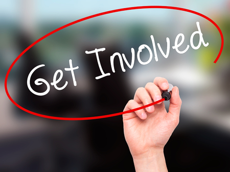 involving: Man Hand writing Get Involved with black marker on visual screen. Isolated on office. Business, technology, internet concept. Stock Photo