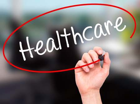 mandate: Man Hand writing Healthcare with black marker on visual screen. Isolated on office. Business, technology, internet concept. Stock Photo