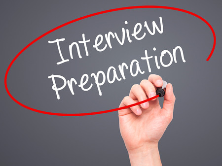 job qualifications: Man Hand writing Interview Preparation with black marker on visual screen. Isolated on grey. Business, technology, internet concept. Stock Photo