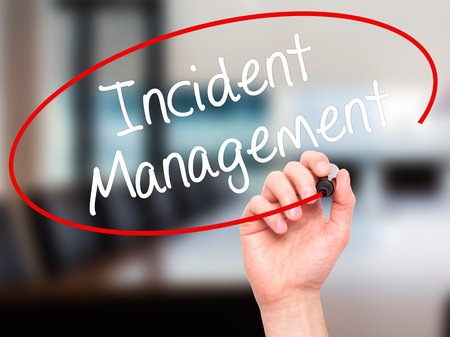 iscp: Man Hand writing Incident Management with black marker on visual screen. Isolated on office. Business, technology, internet concept. Stock Photo