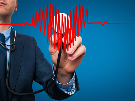 medicaid: Closeup portrait handsome business man, male corporate employee, worker listening to  heart with stethoscope isolated on blue background. Preventive medicine, financial condition check-up concept