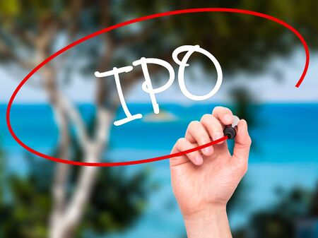publicly: Man Hand writing IPO (Initial Public Offering)   with black marker on visual screen. Isolated on background. Business, technology, internet concept. Stock Photo