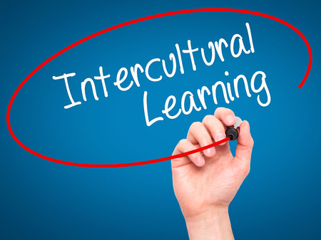 intercultural: Man Hand writing Intercultural Learning with black marker on visual screen. Isolated on blue. Business, technology, internet concept. Stock Photo