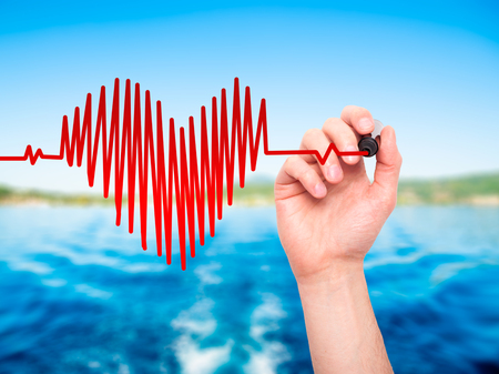 preventive medicine: Closeup of hand drawing  heart beat in heart shape with stethoscope isolated on nature  background. Preventive medicine concept