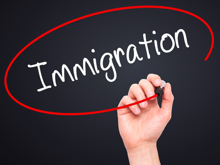 immigrate: Man Hand writing Immigration with black marker on visual screen. Isolated on black. Business, technology, internet concept. Stock Photo Stock Photo