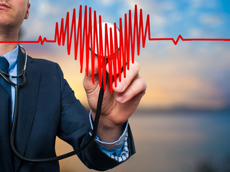 preventive medicine: Closeup portrait handsome business man, male corporate employee, worker listening to  heart with stethoscope isolated on nature background. Preventive medicine, financial condition check-up concept