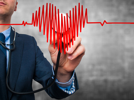 preventive medicine: Closeup portrait handsome business man, male corporate employee, worker listening to  heart with stethoscope isolated on grey background. Preventive medicine, financial condition check-up concept Stock Photo