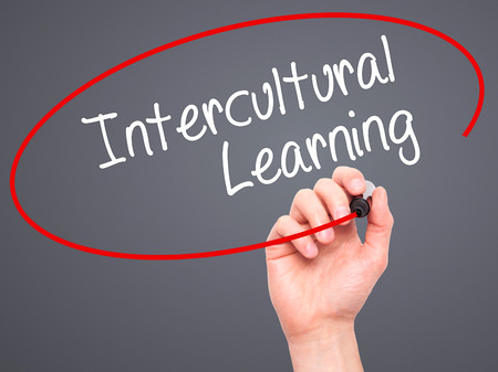 intercultural: Man Hand writing Intercultural Learning with black marker on visual screen. Isolated on grey. Business, technology, internet concept. Stock Photo Stock Photo