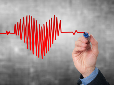 medical decisions: Businessman hand drawing chart heartbeat. Isolated on grey background. Stock Image Stock Photo